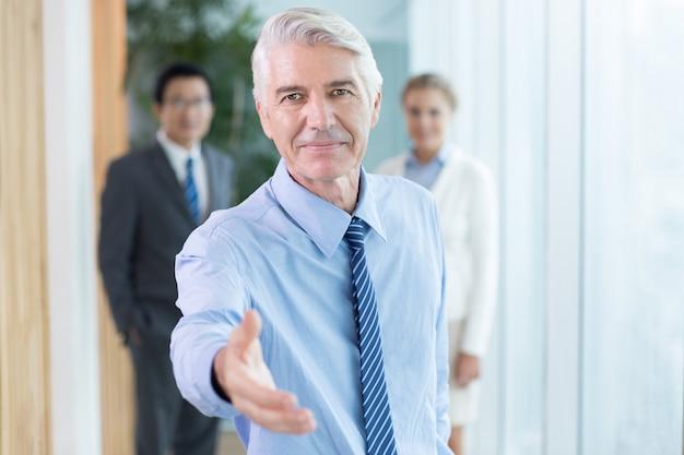 握手のために手を拡張する深刻なビジネスマン