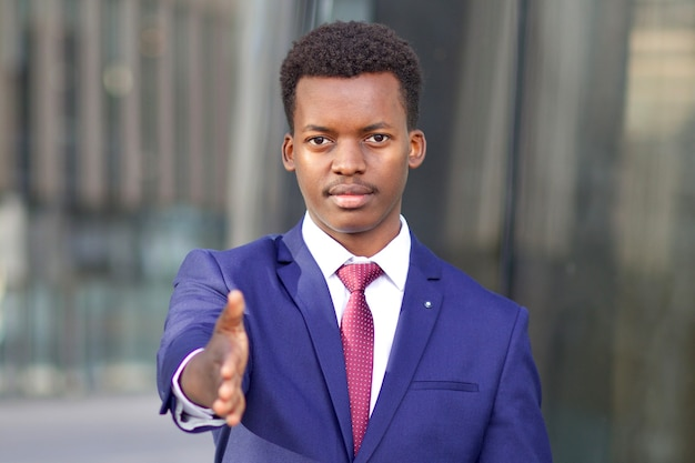 Serious businessman in formal suit suggest, giving hand, palm for business handshaking, greeting. young black african afro american guy with open hand