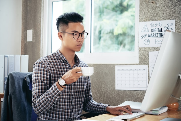 Serious businessman in glasses drinking morning coffee and reading e-mails from colleagues and clients on computer screen