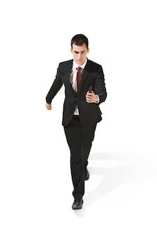 真面目なサラリーマンが白いスタジオ背景に携帯電話で行きます。スーツで幸せな若い男。ビジネス、キャリア、成功、勝利のコンセプト。人間の顔の感情