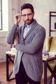真面目なビジネスマンハンサムな素敵なひげを生やした男があなたを見ながら彼の眼鏡に触れています