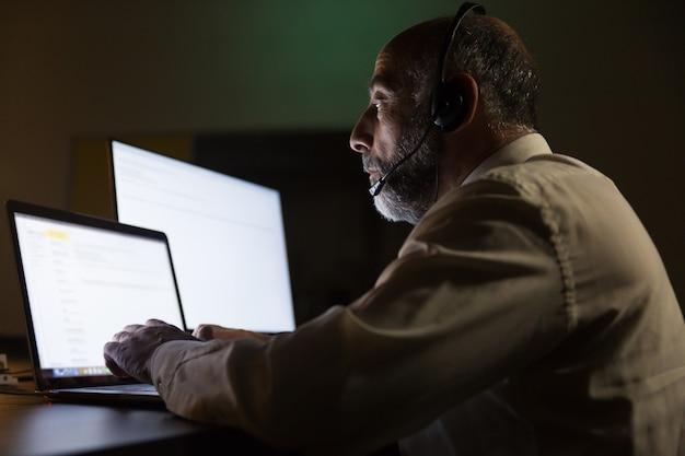 Uomo d'affari serio in cuffia avricolare facendo uso del computer portatile