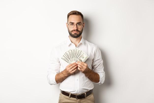 お金を持って、ドルを示して、白い背景の上に立っている深刻なビジネスマン