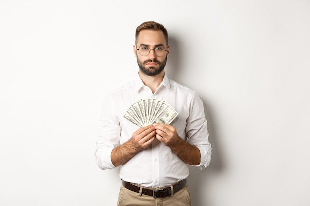 Serious businessman holding money, showing dollars, standing over white background.