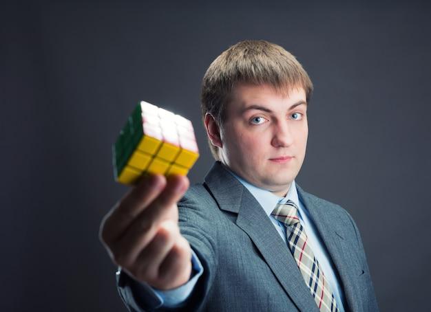 Серьезный бизнесмен, держа в руках кубик рубика