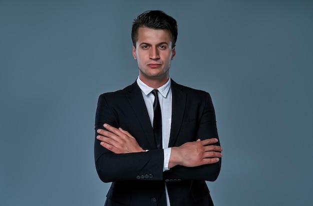灰色の背景に分離された黒いスーツを着た真面目なビジネスマン。腕を組んで立っているハンサムな男。