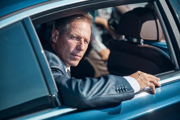 フォーマルなスーツを着た真面目なビジネスマンが空港からの移動中に自動車の窓の外を見ています