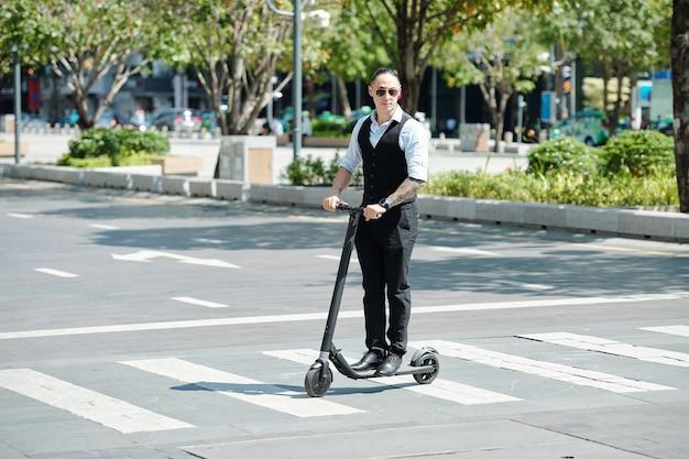 交差点で電動スクーターに乗ってサングラスの真面目なビジネスマン
