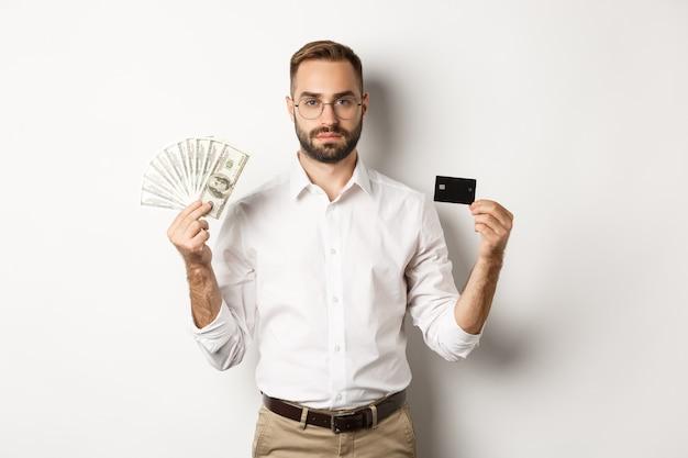 カメラを見て、クレジットカードとお金を持って、白い背景の上に立っている真面目なビジネスマン。ショッピングと金融の概念