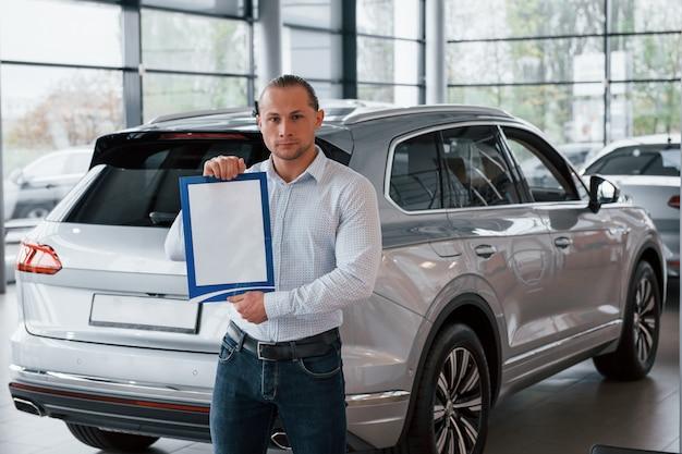 真面目なサラリーマン。マネージャーは紙と書類を手に、現代のシルバー色の車の前に立っています。