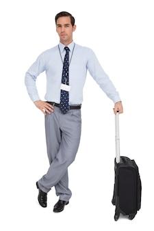 Серьезный бизнесмен рядом с его чемоданом