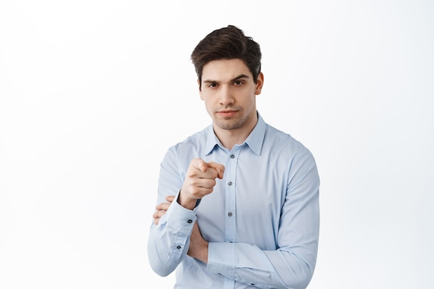 Serious businessman pointing at front, talking to you, choosing employee, inviting to work in his company, standing over white wall