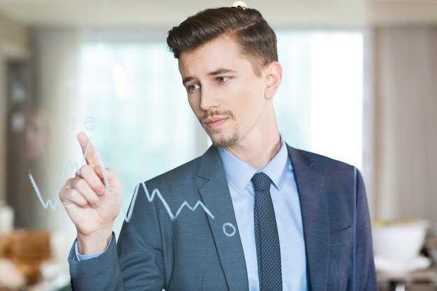 Serious businessman pointing to graph on glass