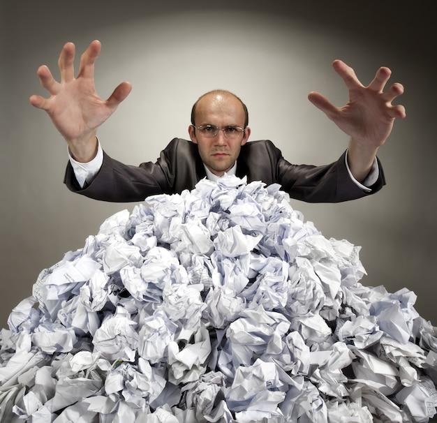 Серьезный бизнесмен тянется к мятым бумагам