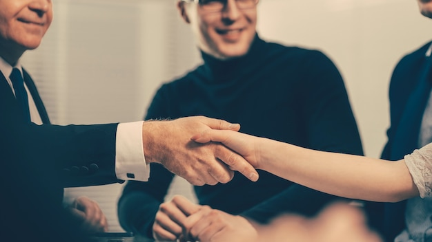 Serious businessman shaking hands with a young business man during a business meeting