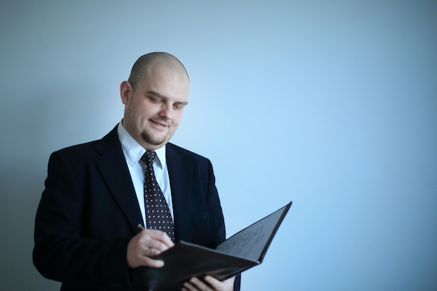 深刻なビジネスマンは、灰色の背景に分離された文書に署名します。コピースペースのある写真。