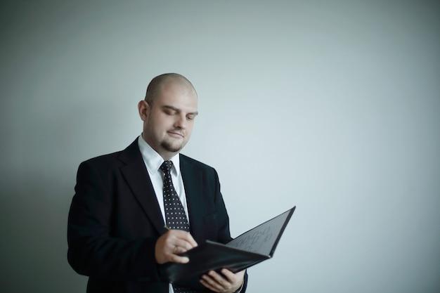 深刻なビジネスマンは、灰色の背景で隔離の文書に署名します。