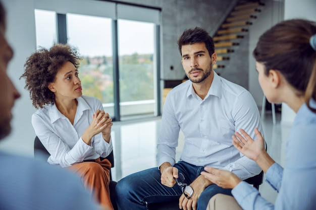 Serious businessman sitting in circle with support group and talking about problems.