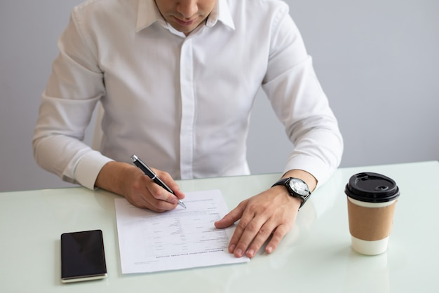 Serious businessman sitting at table and filling in application