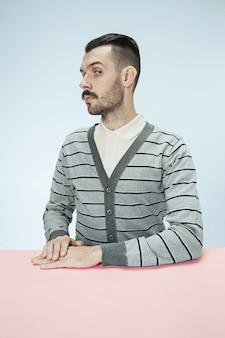 Uomo d'affari serio che si siede al tavolo. il ritratto in stile minimalista di profilo