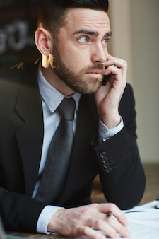 Serious businessman speaking on phone in office