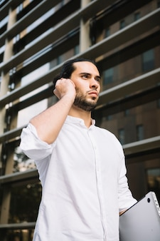 Serious businessman standing in front of building talking on bluetooth