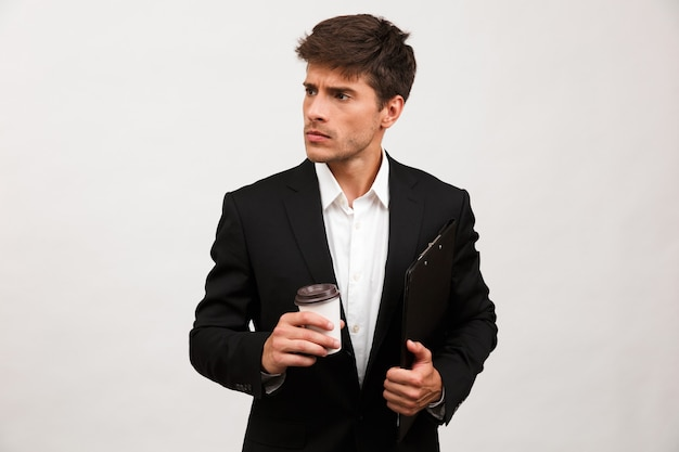 Serious businessman standing isolated holding clipboard looking aside drinking coffee.