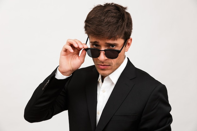Serious businessman standing isolated wearing sunglasses.