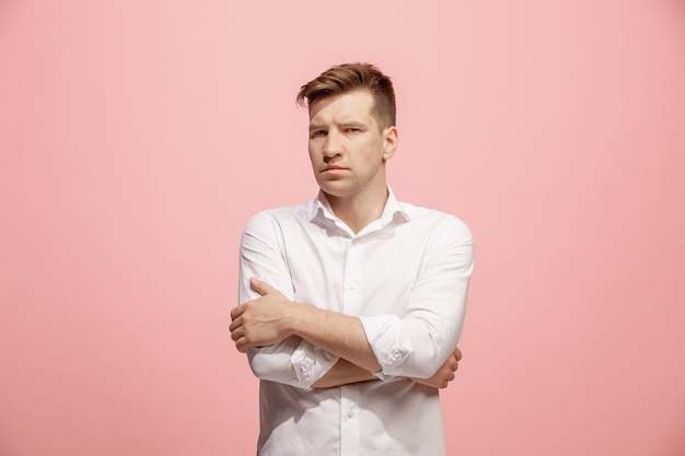 Serious businessman standing and looking at camera against pink wall.
