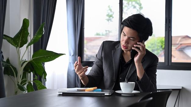 Серьезный бизнесмен разговаривает по мобильному телефону со своим деловым партнером.
