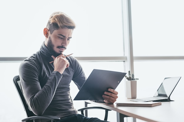 Serious businessman thinking hard of problem solution working in office with computer, documents, thoughtful trader focused on stock trading data analysis, analyzing forecasting financial rates