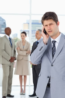 Serious businessman using a cell phone while his team is behind him