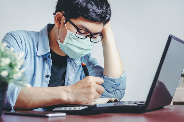 Serious businessman wearing a mask working at home
