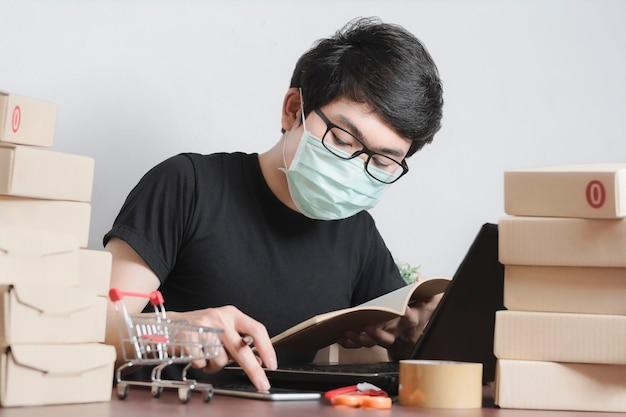 カジュアルな服装でマスクを身に着けている真面目なビジネスマン顧客の注文情報を確認し、