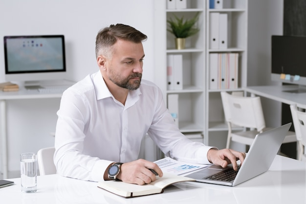 Serious businessman in white shirt looking through data on laptop display while sitting by desk in office
