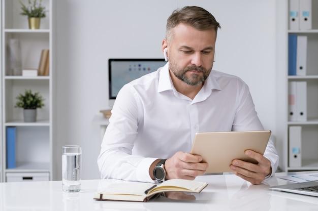 オンラインビデオトレーニング、会議、またはウェビナーを見ながらタッチパッドディスプレイを見ているエアポッドを持つ真面目なビジネスマン