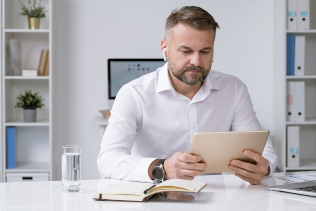 Serious businessman with airpods looking at touchpad display while watching online video training, conference or webinar