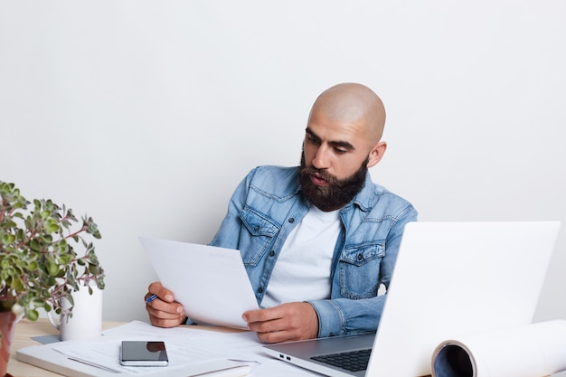 A serious businessman with beard and mustache wearing jean shirt being busy with documents.