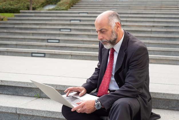 Serious businessman with laptop computer on street