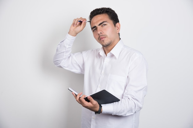Serious businessman with notebook posing on white background.