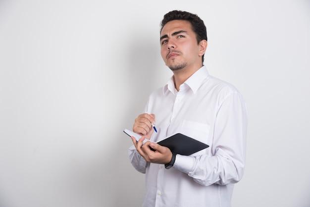 Grave imprenditore con penna e taccuino pensando su sfondo bianco.