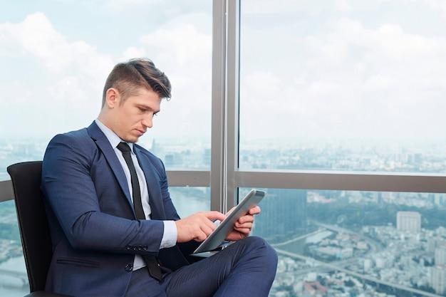 Серьезный бизнесмен, работающий на планшете
