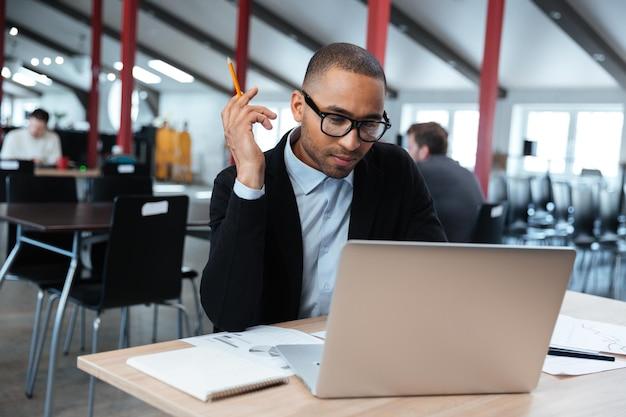 Серьезный бизнесмен, работающий с ноутбуком в офисе, держа карандаш