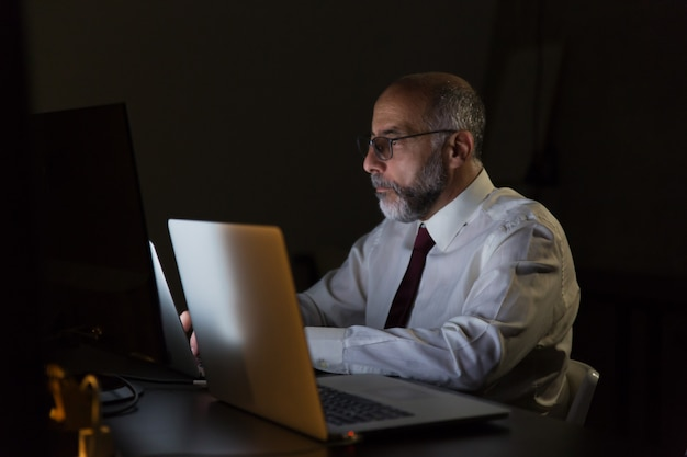 Serious businessman working with laptop late at night
