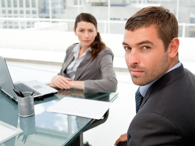 テーブルの周りに座ってカメラを見ている真剣なビジネスマン