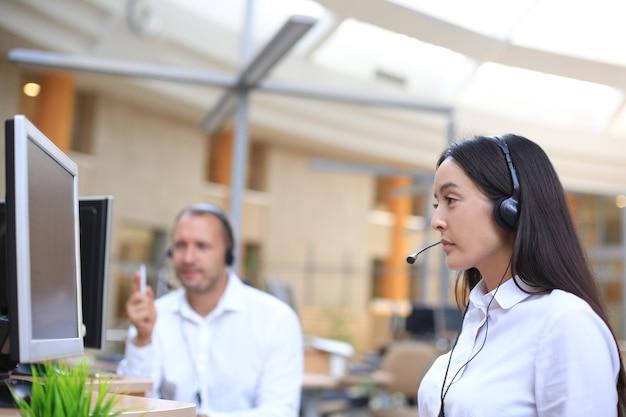Серьезная бизнес-леди в наушниках смотрит веб-семинар на ноутбуке, делает заметки, изучает компьютерный курс, звонит, участвует в онлайн-конференции, переводчик переводит учебный класс