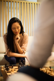 Serious businesswoman playing chess with male colleague