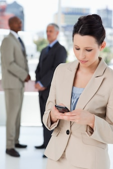 Serious businesswoman sending a text and executives behind her