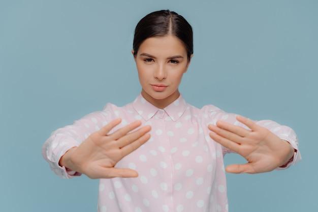 Serious businesswoman shows refusal gesture