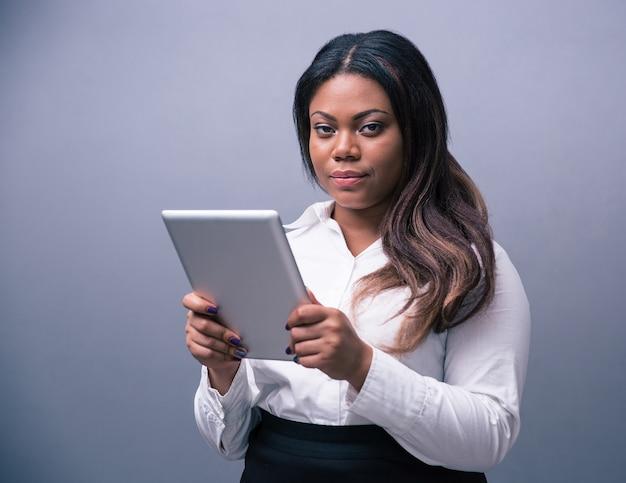 Серьезная деловая женщина, стоящая с планшетным компьютером